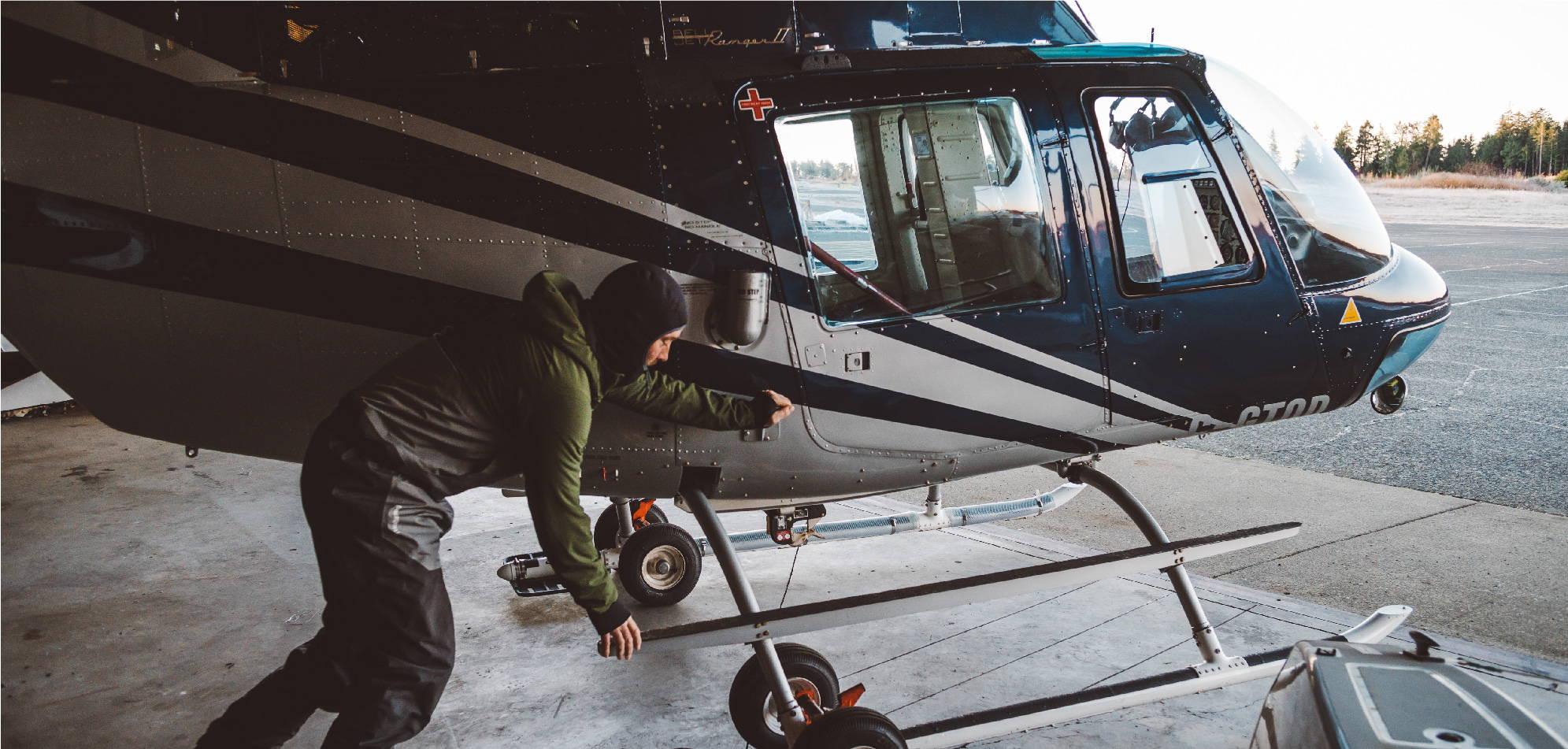Jeremy Koreski pushing helicopter in hanger | Rumpl