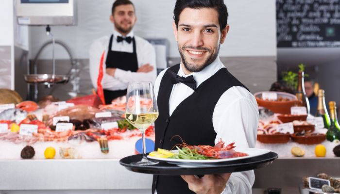 Caterer wearing black bow tie and vest with food display