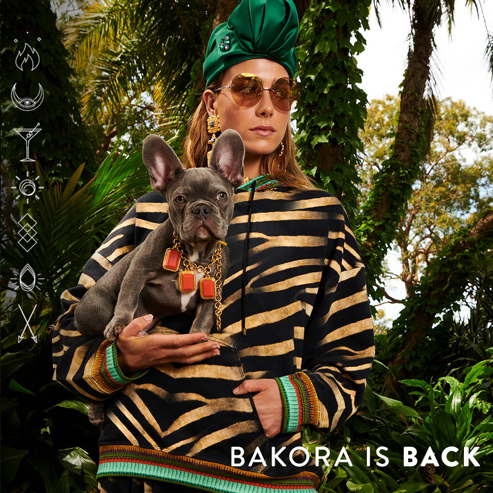 Bakora Is Back | Model in black and beige hoodie holding dog