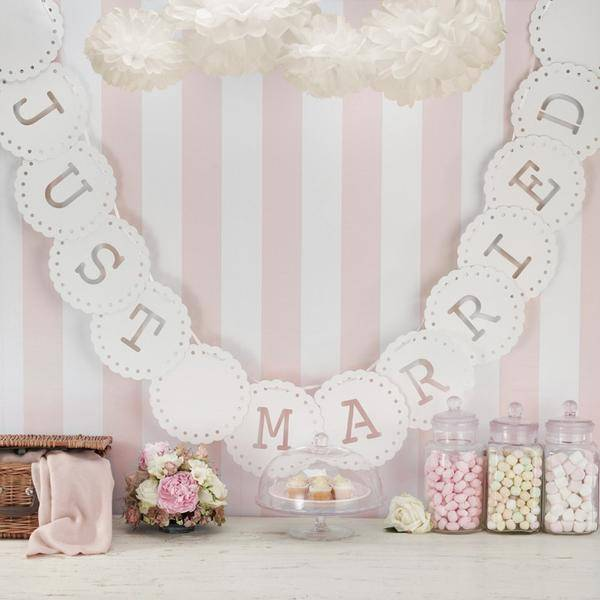 A photo of a 'just married' wedding banner hung over a table with vintage-style sweet-jars filled with sweets, a cake stand, a floral centrepiece and a rustic wedding basket