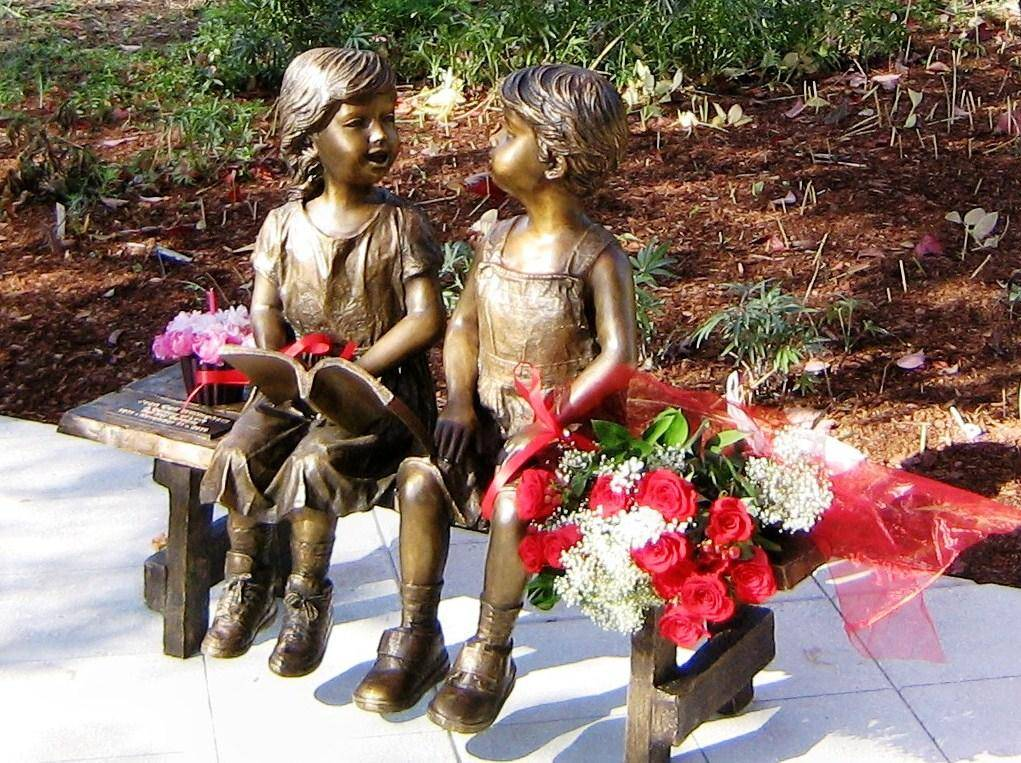 Bronze garden statue of children on a bench reading a book