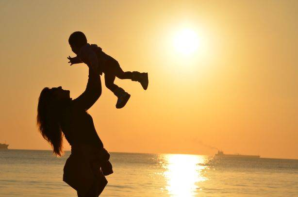 Woman Holding Baby Up In The Air By The Sea & Sunset