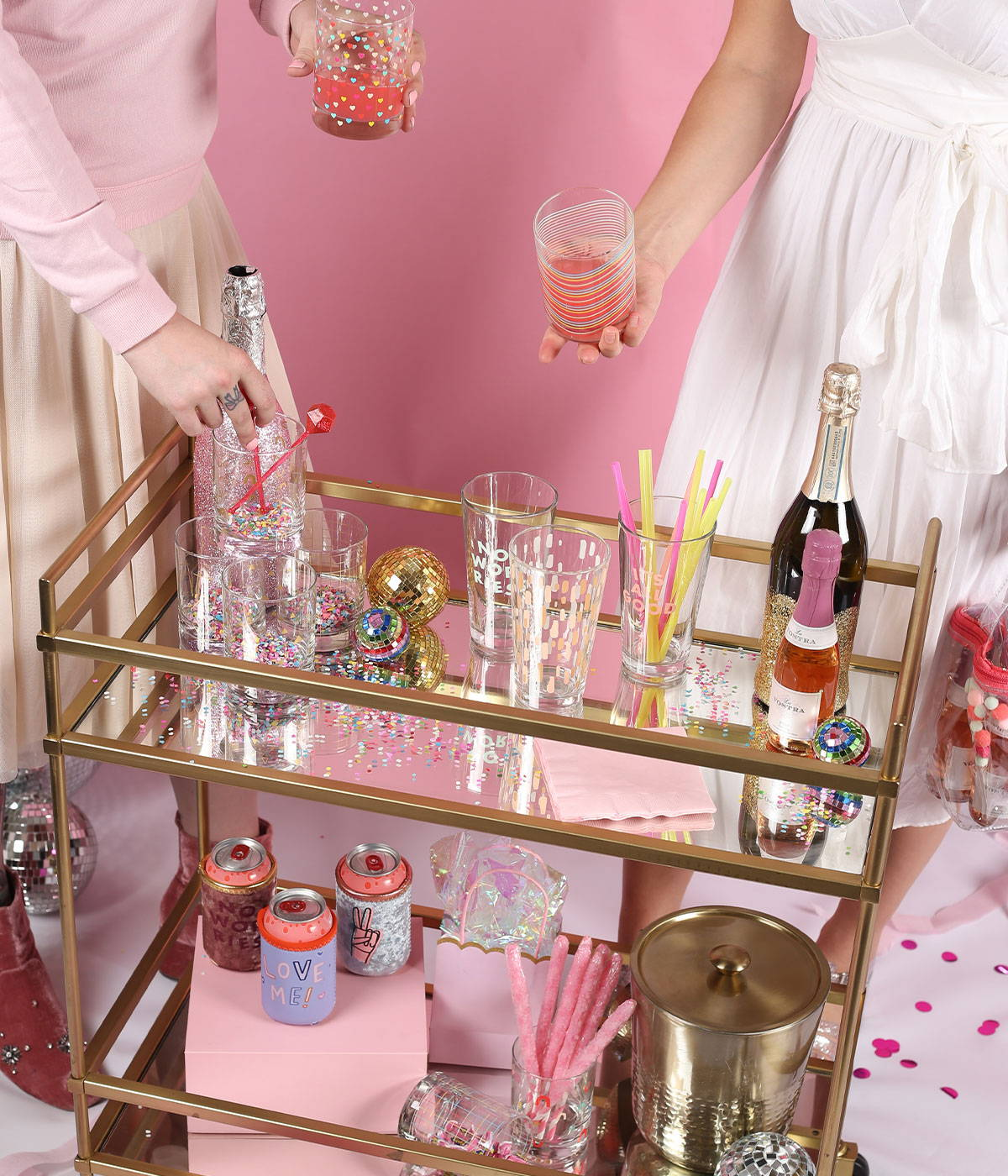 A bar cart with cute glassware and girls holding cute rocks glasses.