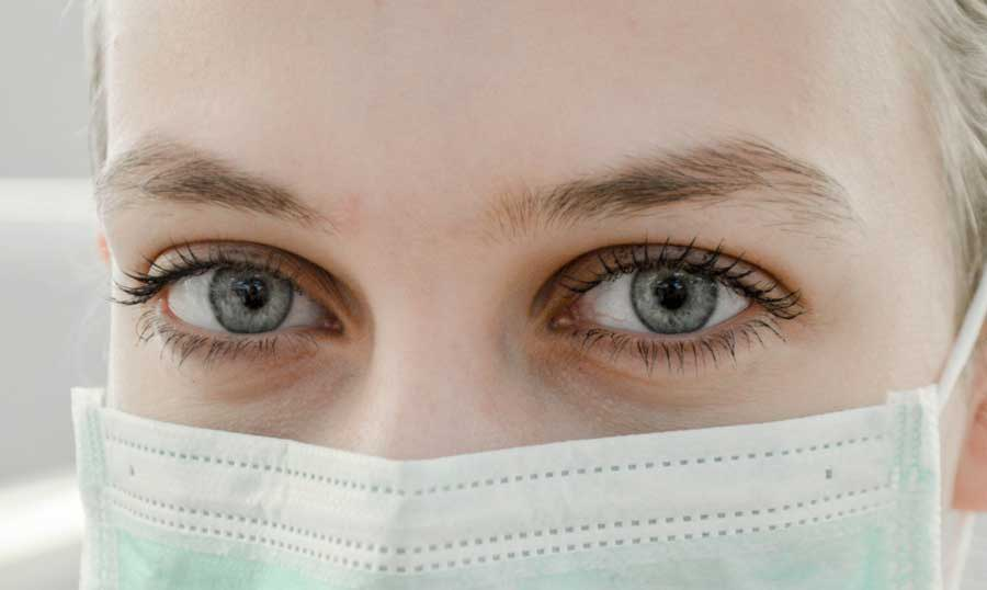 Photo of a person's eyes close up wearing a medical mask in a blog about diabetes facts