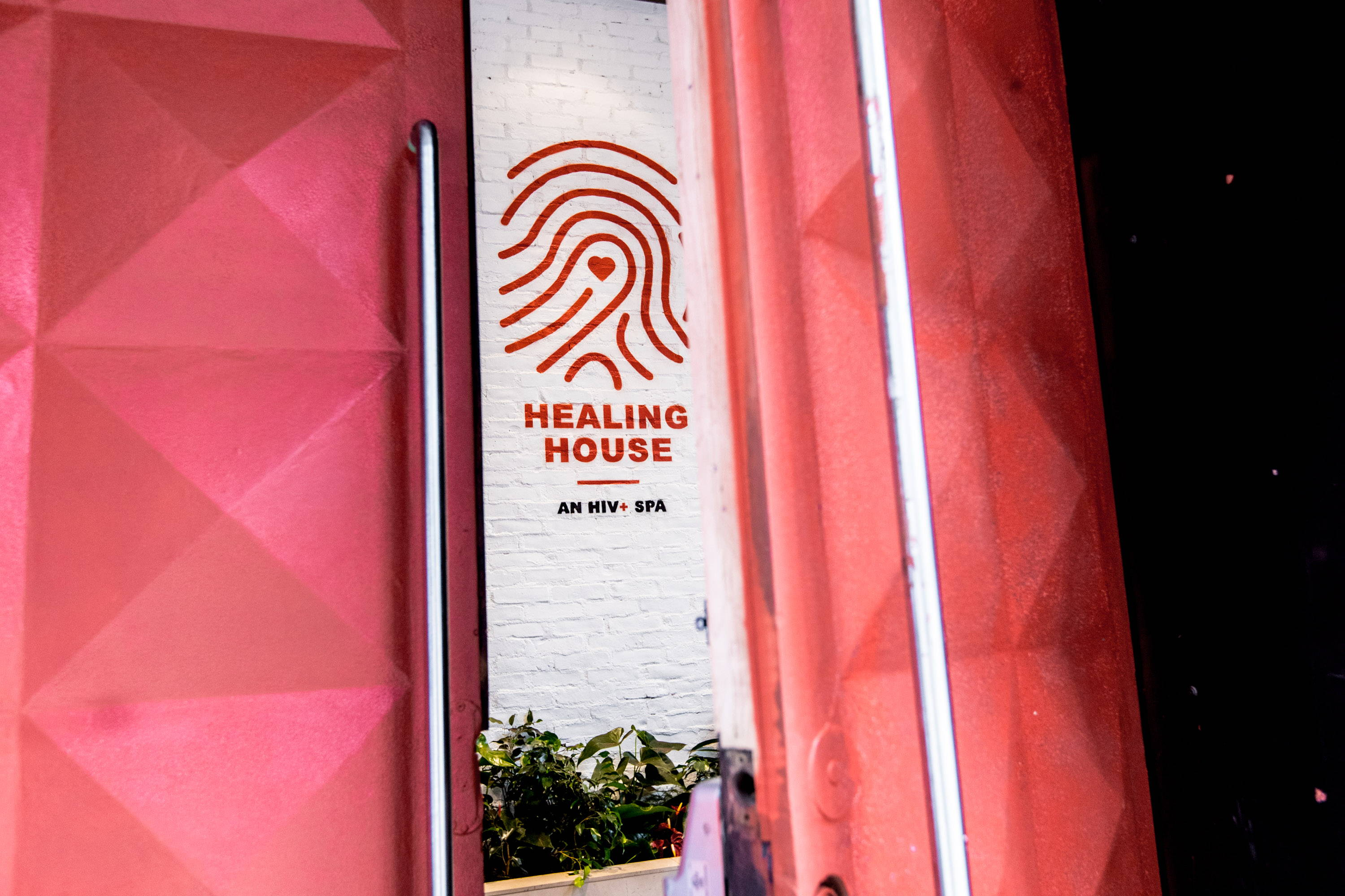 healing house, an HIV+ Spa logo and text in red on white brick wall in between two red doors