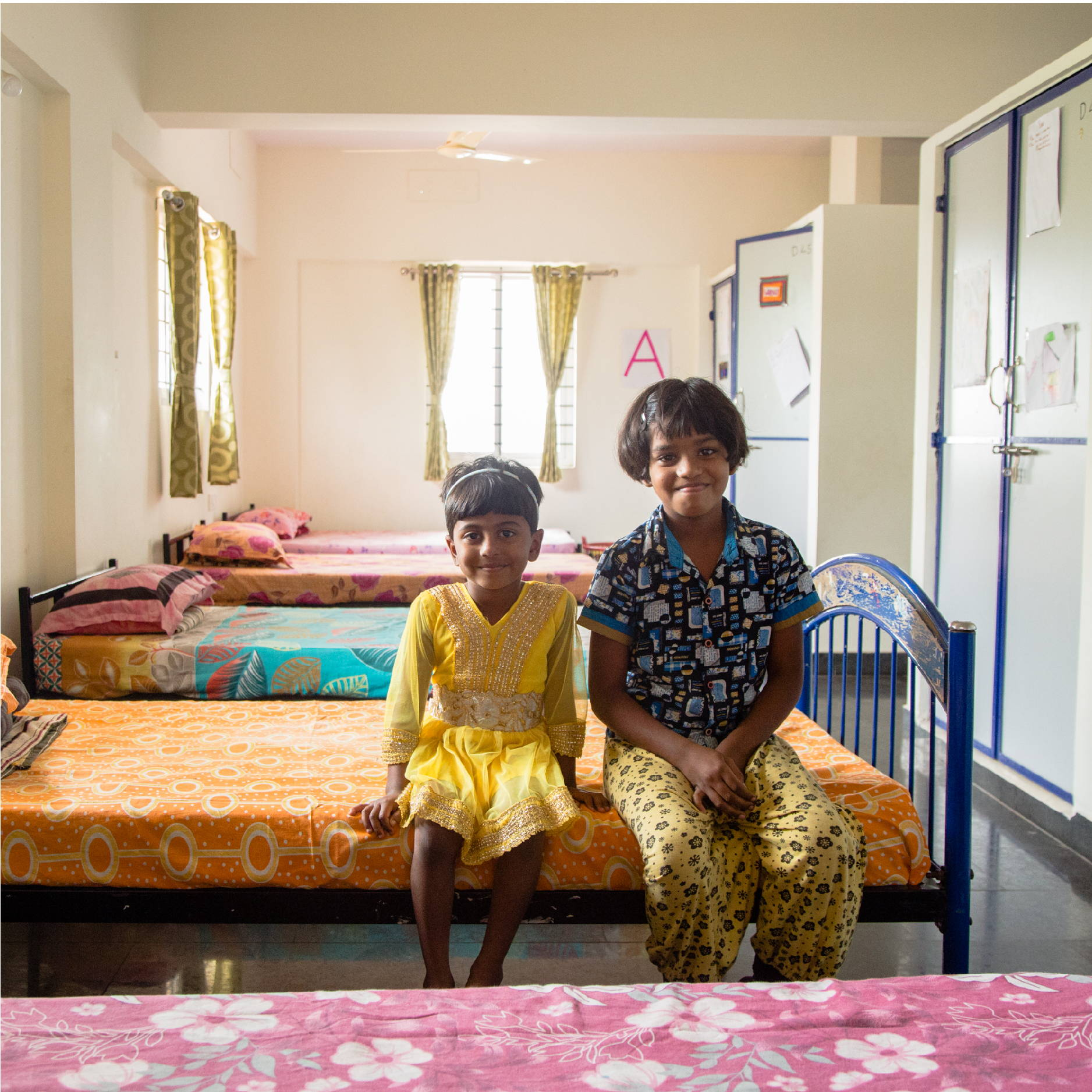 Two Indian girls sit on their beds in a children's home in Bangalore India.