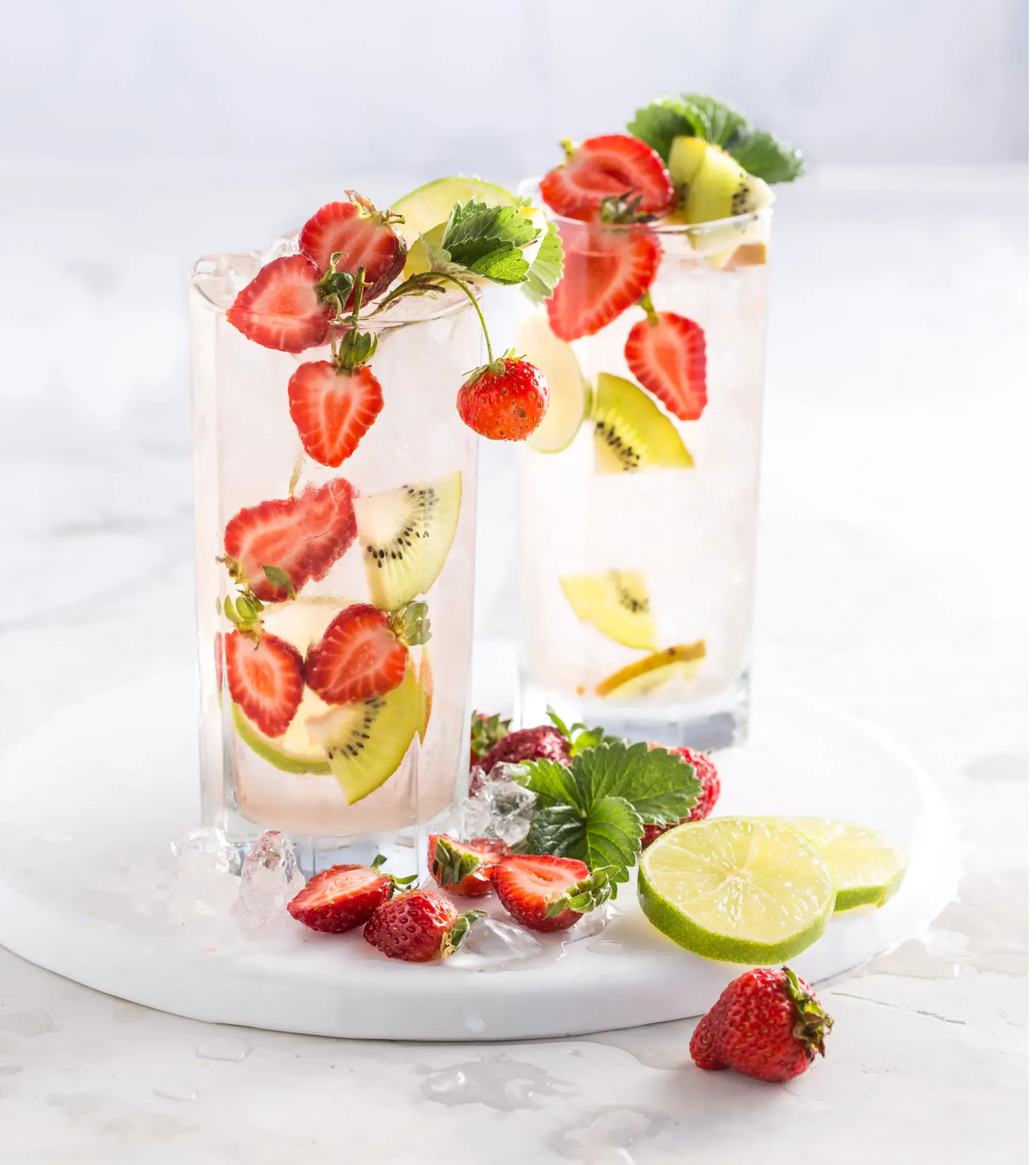Iced water with sliced strawberries and kiwi inside