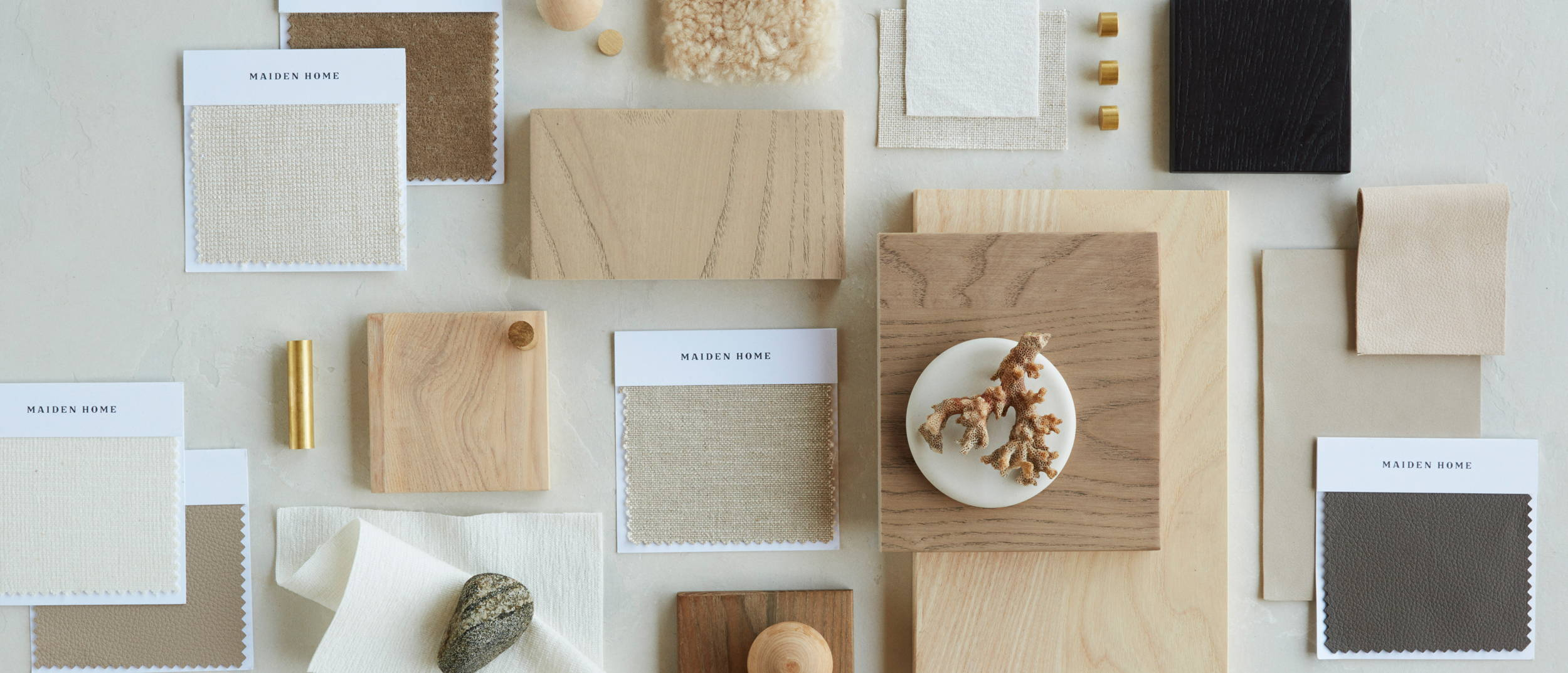 A laydown of various materials and swatches, including fabrics, leathers, woods, and brass.