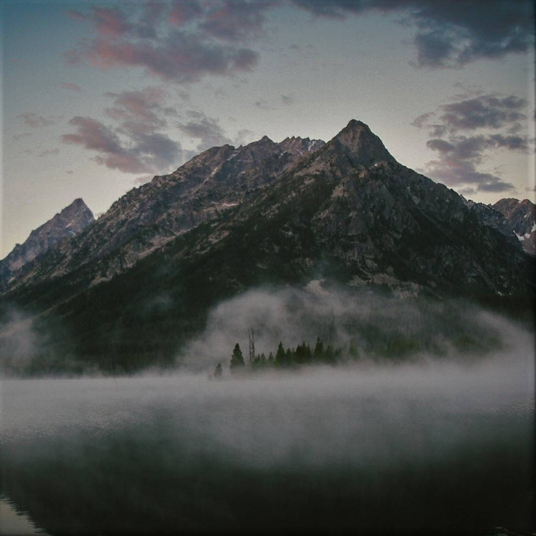 A misty mountain range with forests in the foreground