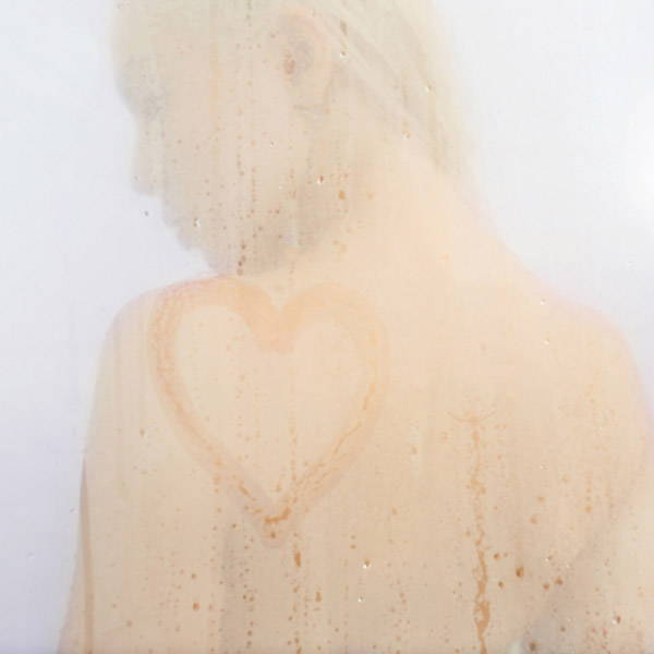 Woman behind a misted shower door on which a heart is painted