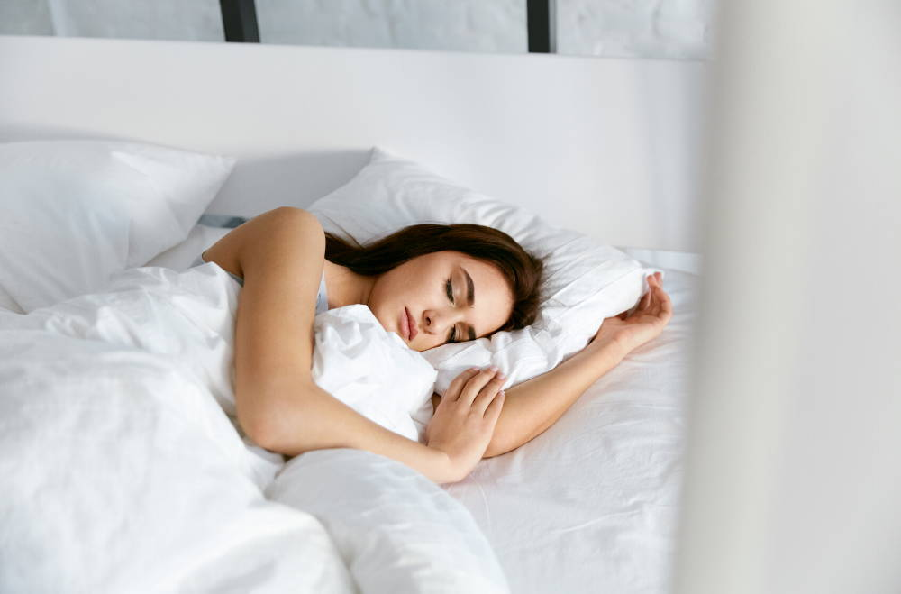 woman sleeping in bed with white sheets|How Not Getting Enough Sleep Can Ruin Your DNA, Microbiome, and Shorten Your Life