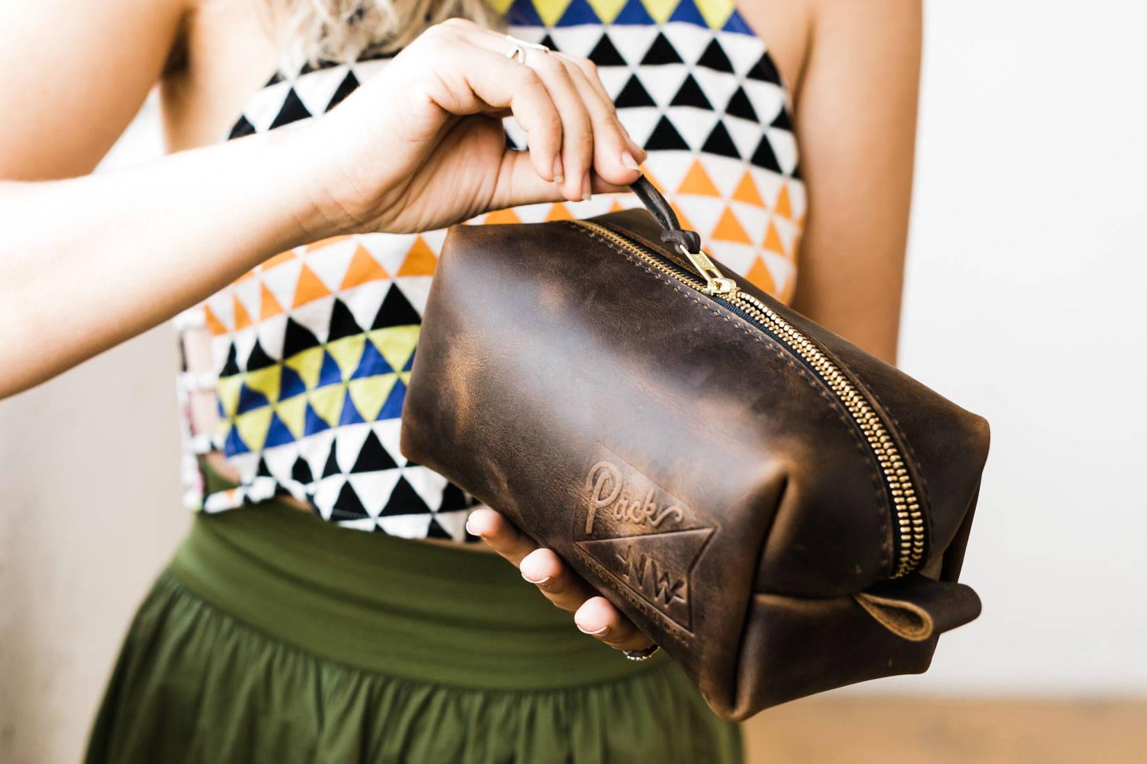 woman unzipping a corporate branded dopp kit