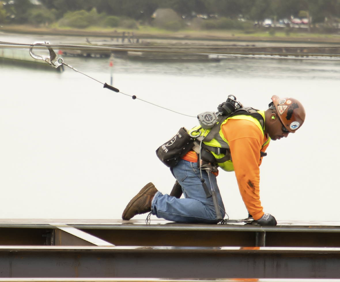 Construction worker bending down that has a DuraTech Personal Leading Edge twin-leg self-retracting lifeline attached to his harness