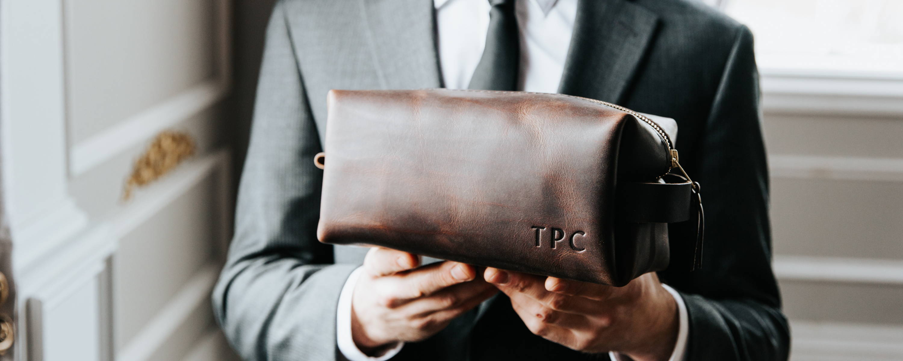 man in a groomsman suit holding out a handmade grizzly leather dopp kit from portland leather goods