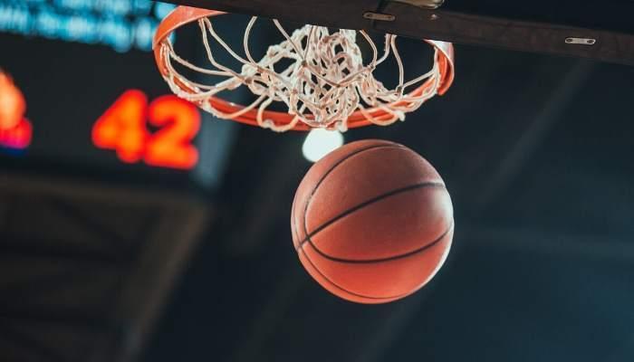Basketball going through hoop at indoor stadium