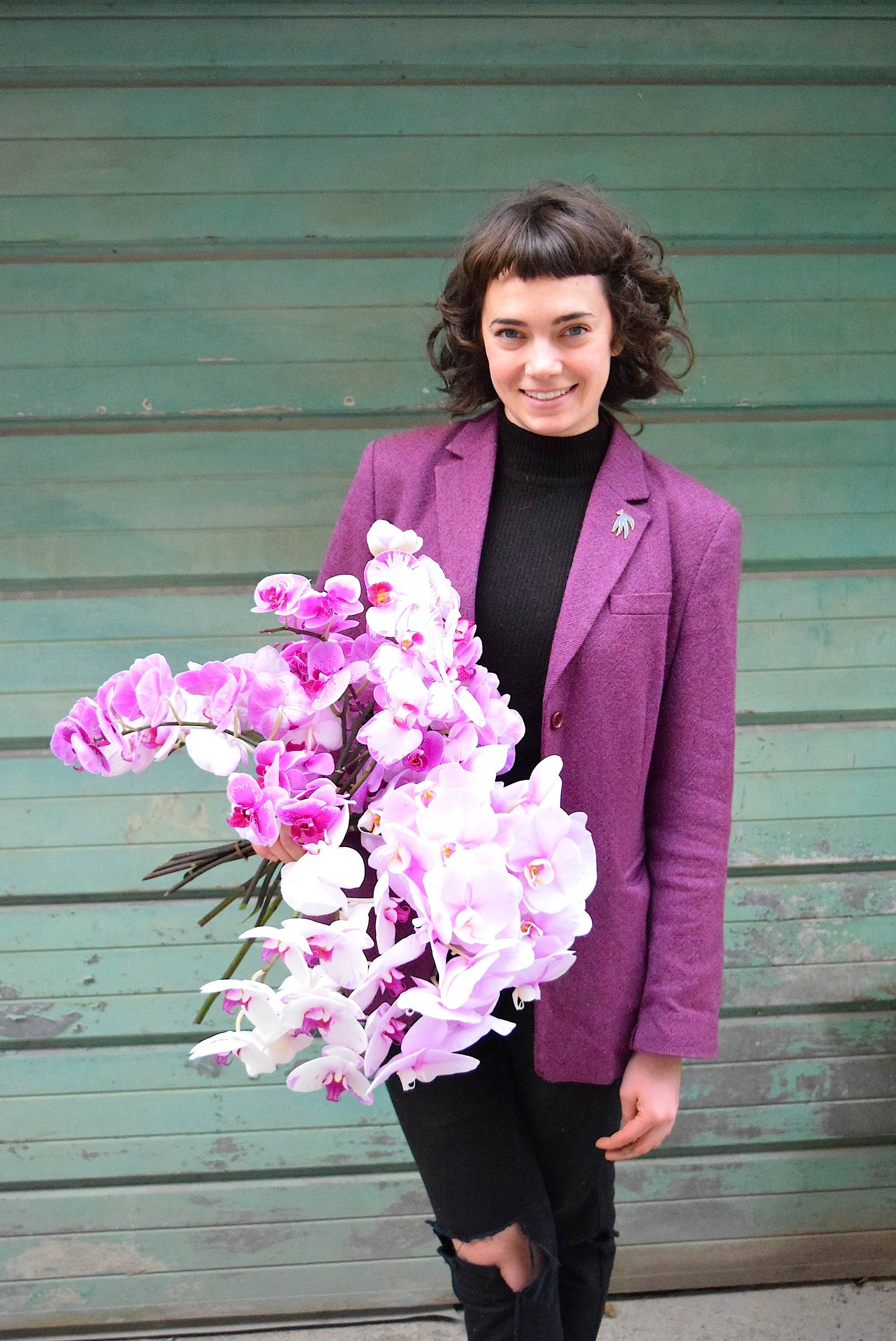 Bethany Rose Puttkemery, Lead Designer at Wild North Flowers holding orchids