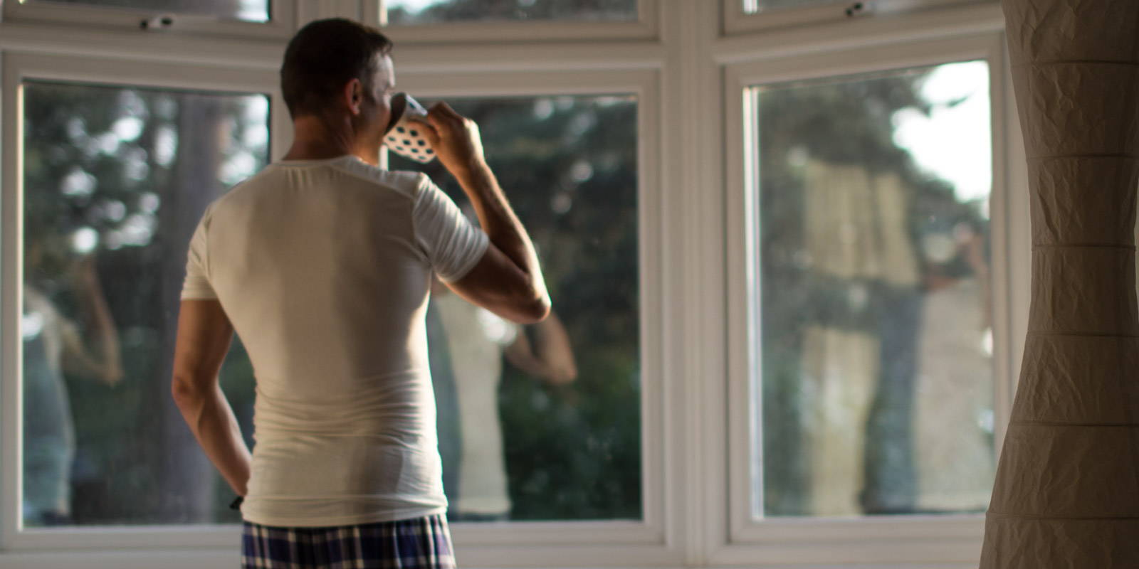 A picture of a man drinking tea, looking out of his bedroom window, wearing a white undershirt and blue checked cotton trousers