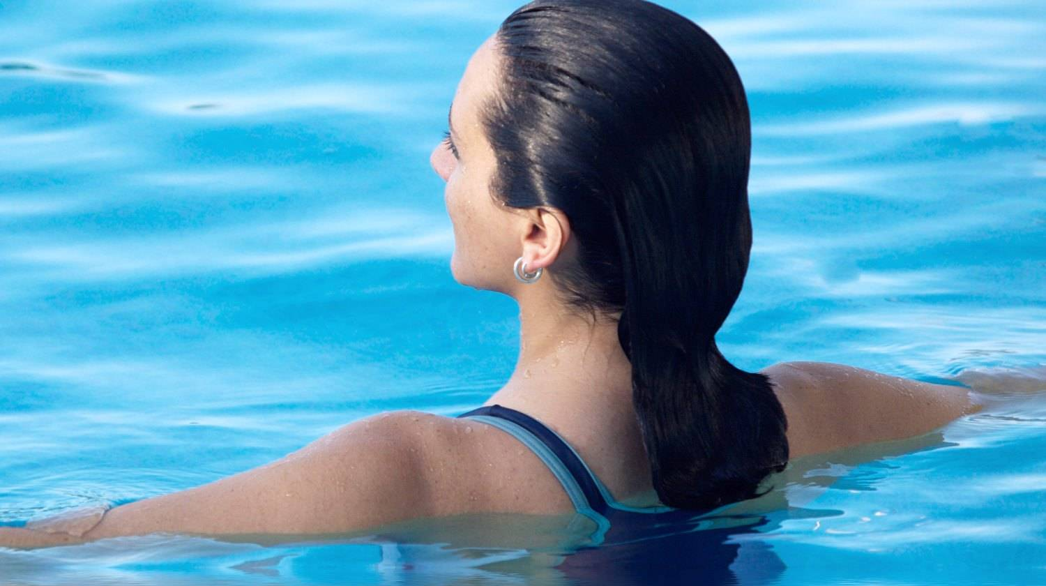 Woman in a swimming pool and her reflection | Health Benefits of Water Running You Should Know! | Featured | deep water running benefits