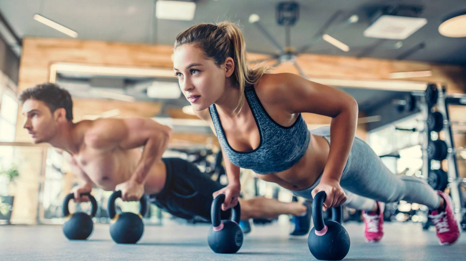 Young couple is working out at gym | Protein Powder Isolate vs. Concentrate: Which Is the Healthiest? | milk protein | Featured