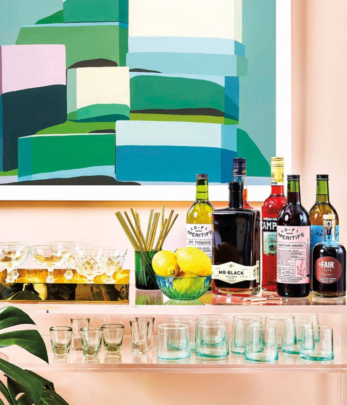 A colorful set of bottles and glasses on a barcart in front of art painting.