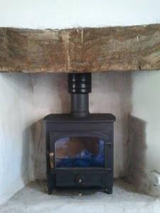 Wood burning stove shield wood lintel