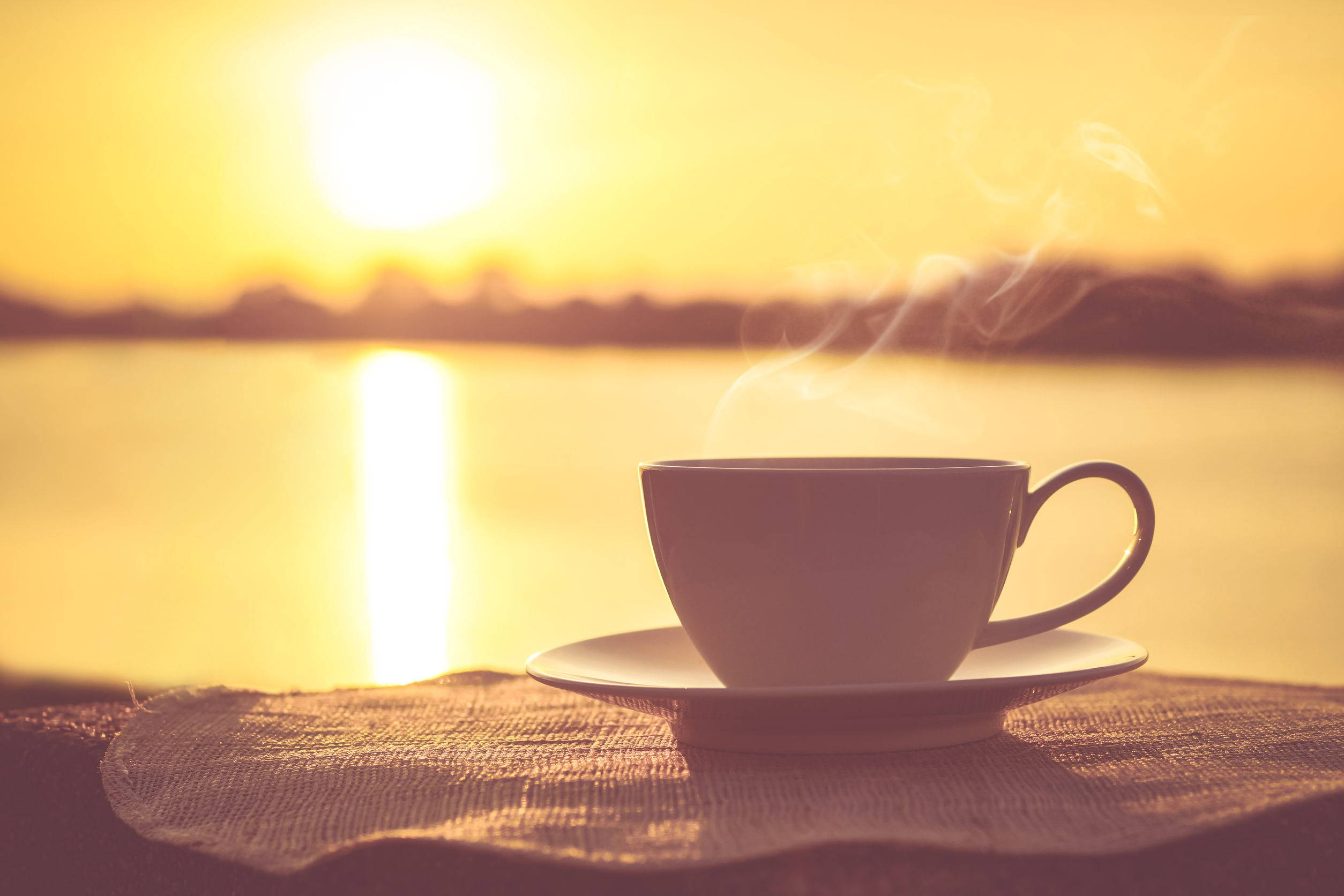 A small cup of Perk Energy sitting on a plate outside with a sunrise over a lake in the background