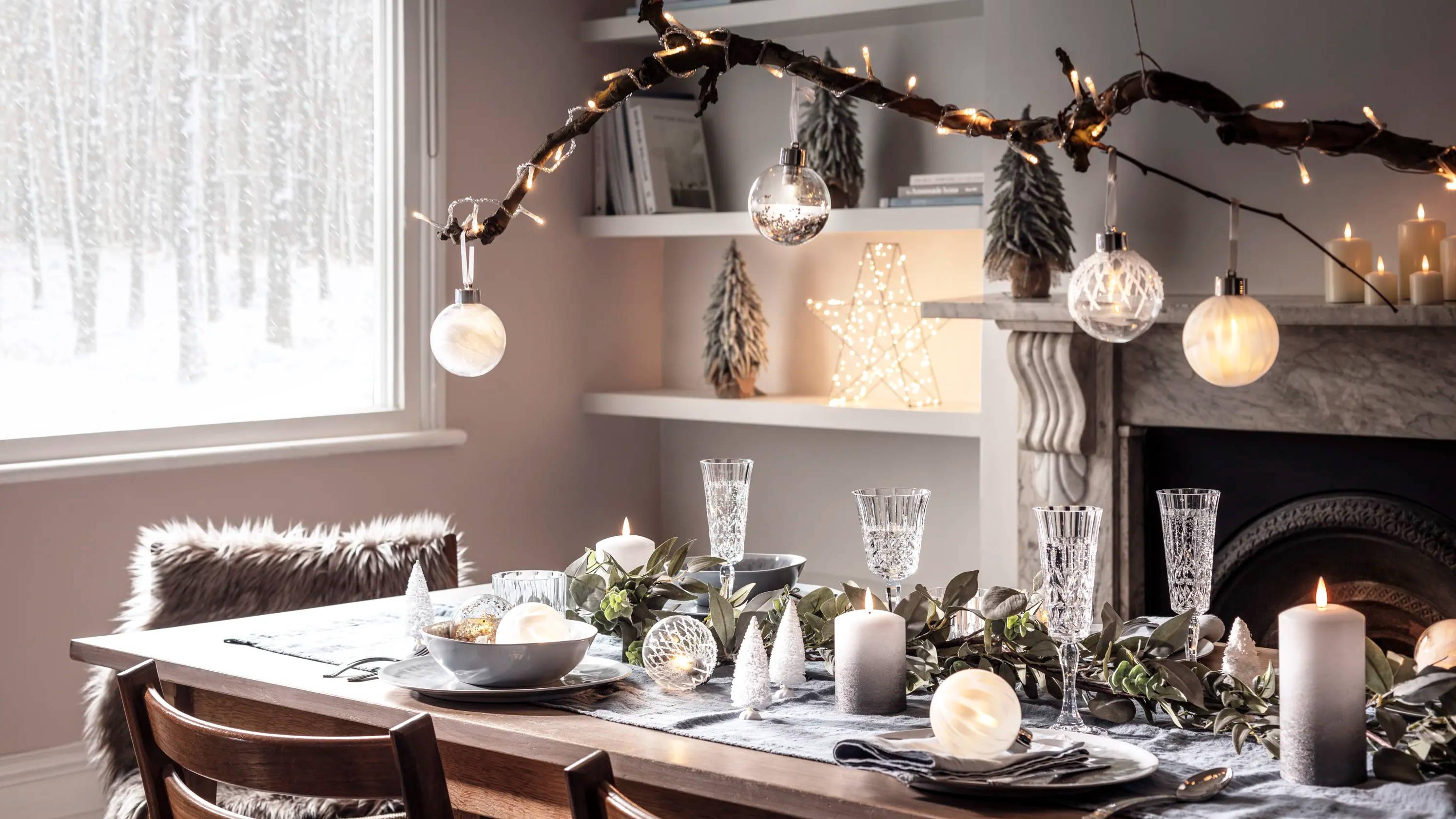 Weihnachtlich gedeckter Tisch mit Baumkugeln an Ast.