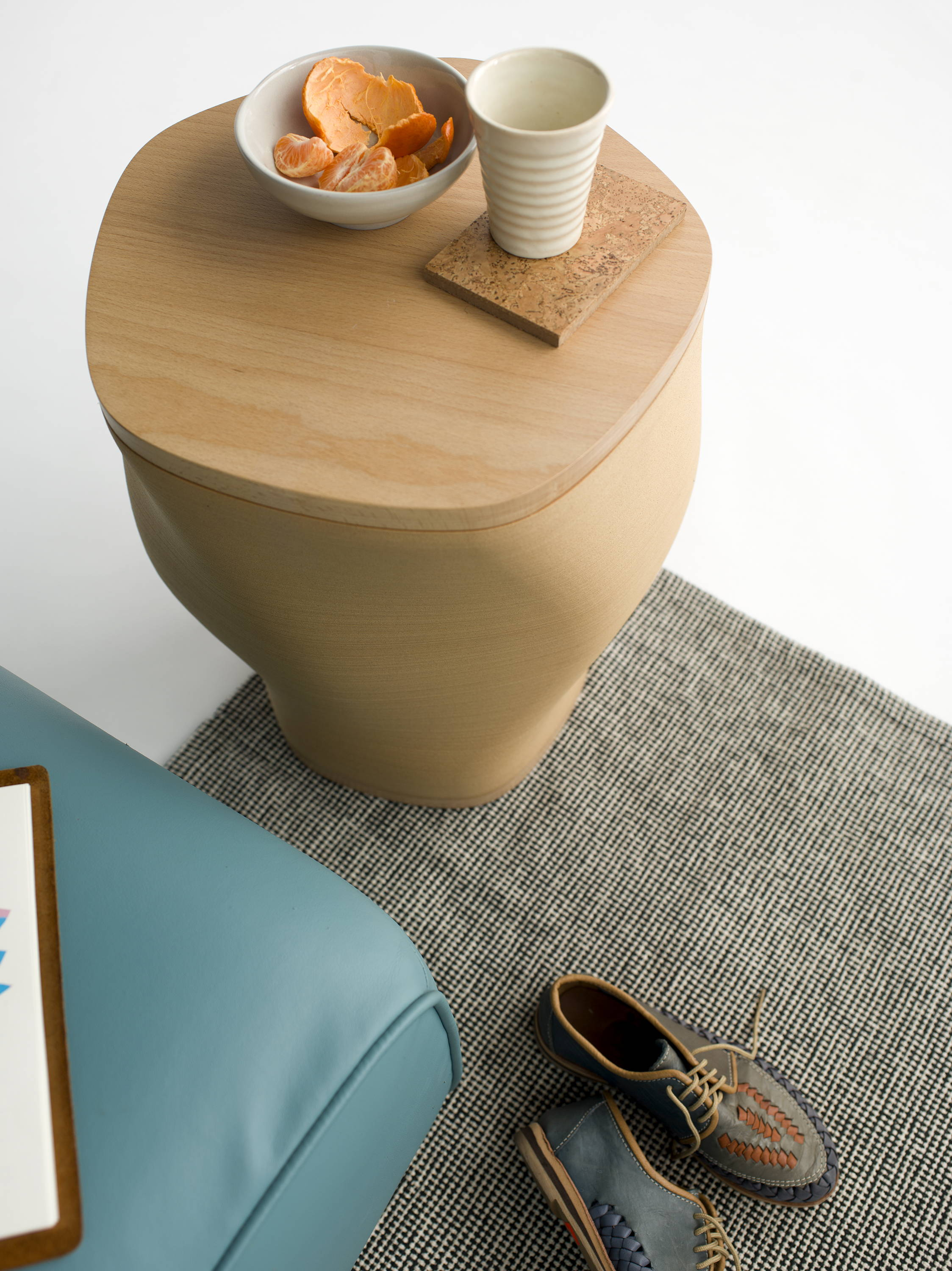 Side table made of hardwood and wood fiber with food bowl and cup on surface