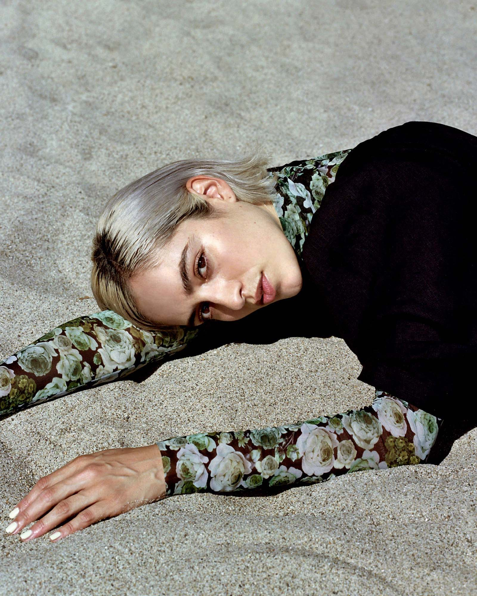 Image of model laying in the sand wearing a Ganni mesh top and Mara Hoffman jumpsuit.