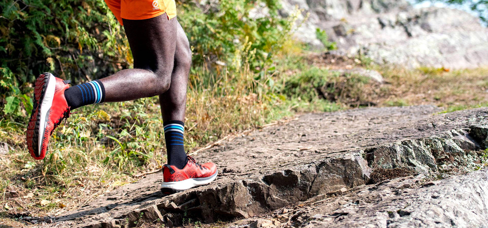A trail runner midstride running up a trail wearing darn touch socks for runners and runners shoes
