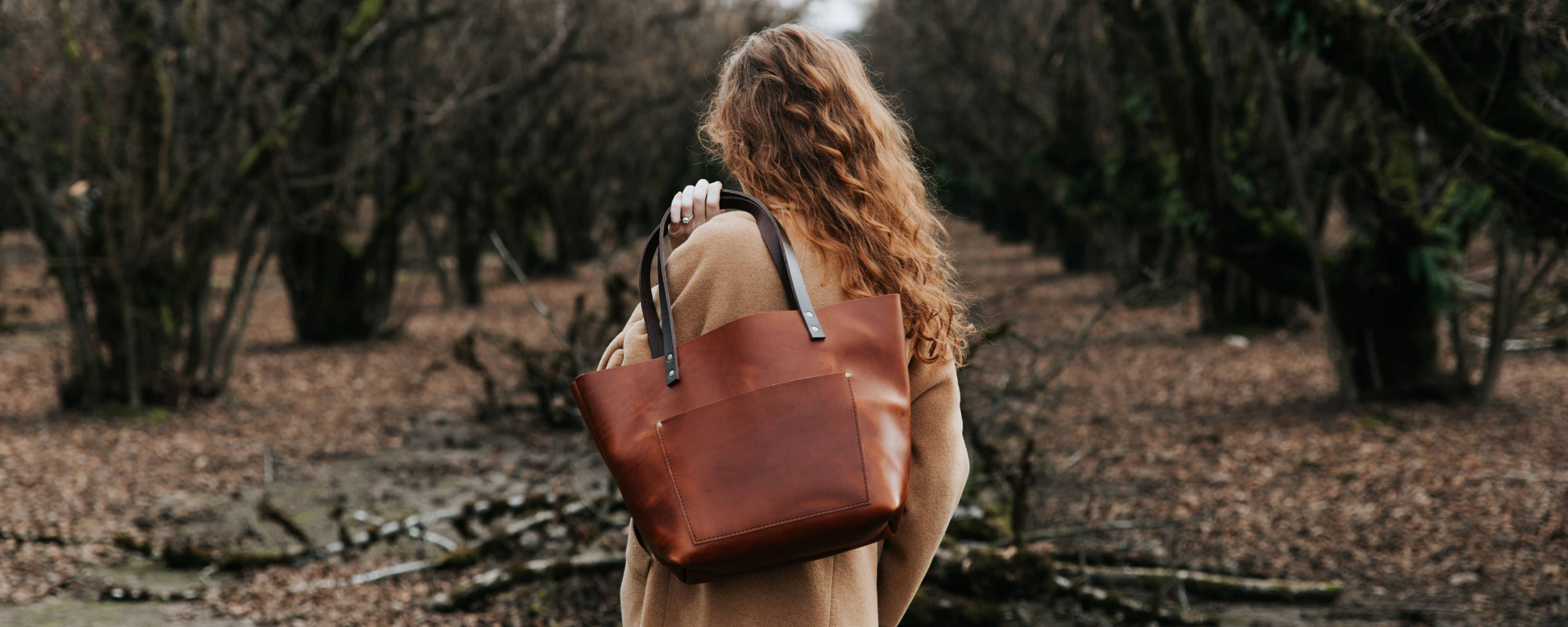leather tote slung over the shoulder of a model walking in the woods