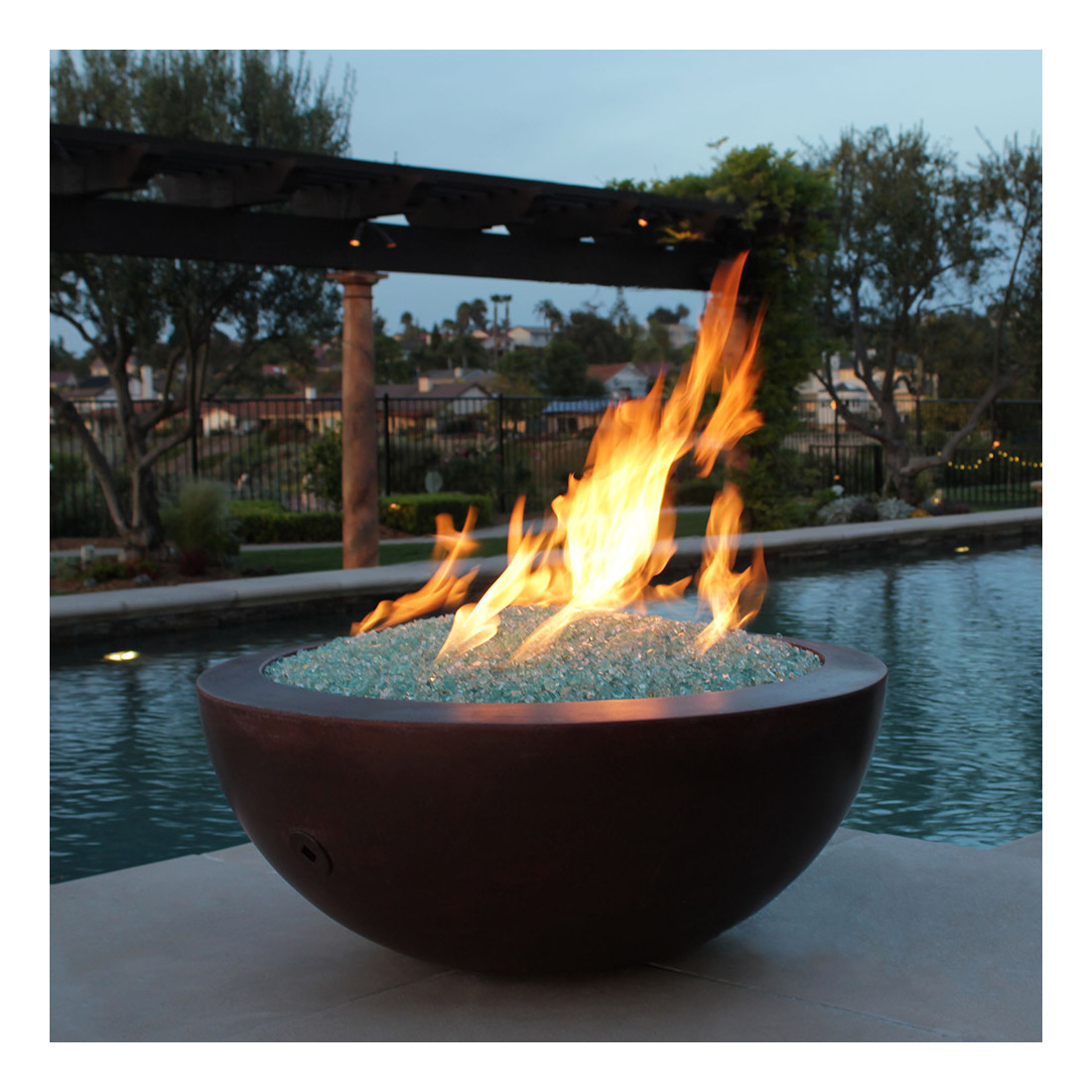 A fire bowl in the evening by a pool