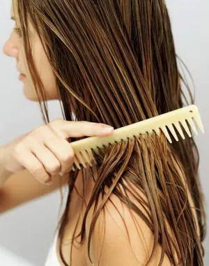 Girl brushing wet hair with comb