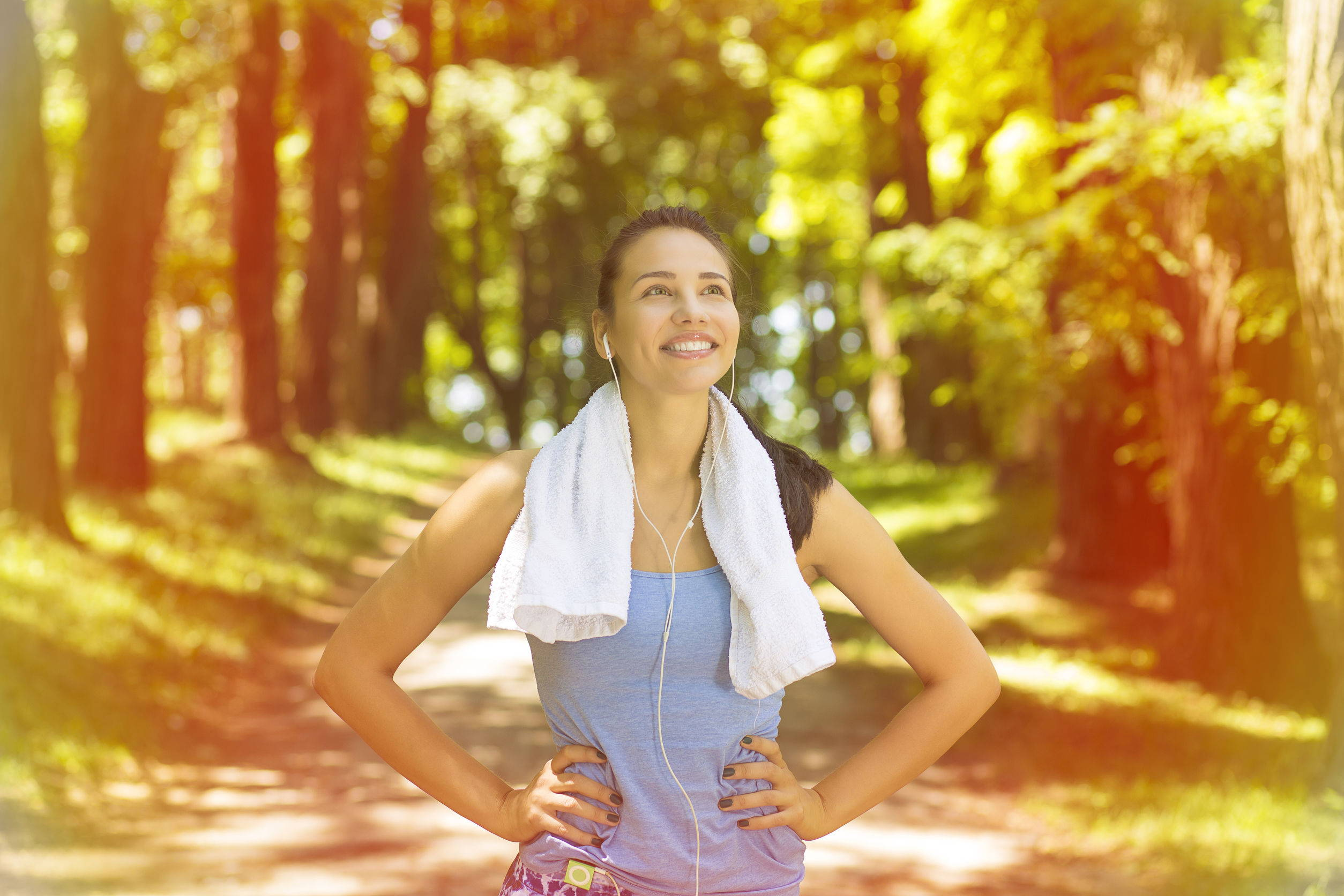 Young woman is energized after a workout and has a towel around her neck.