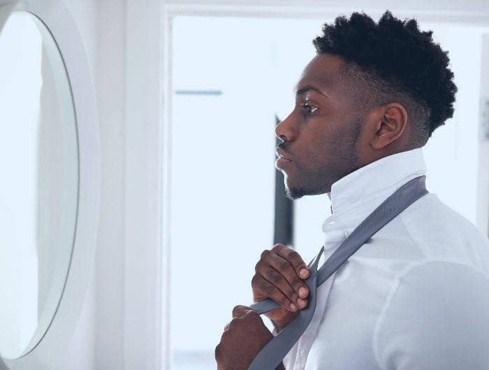 Man looking in mirror and tying a necktie