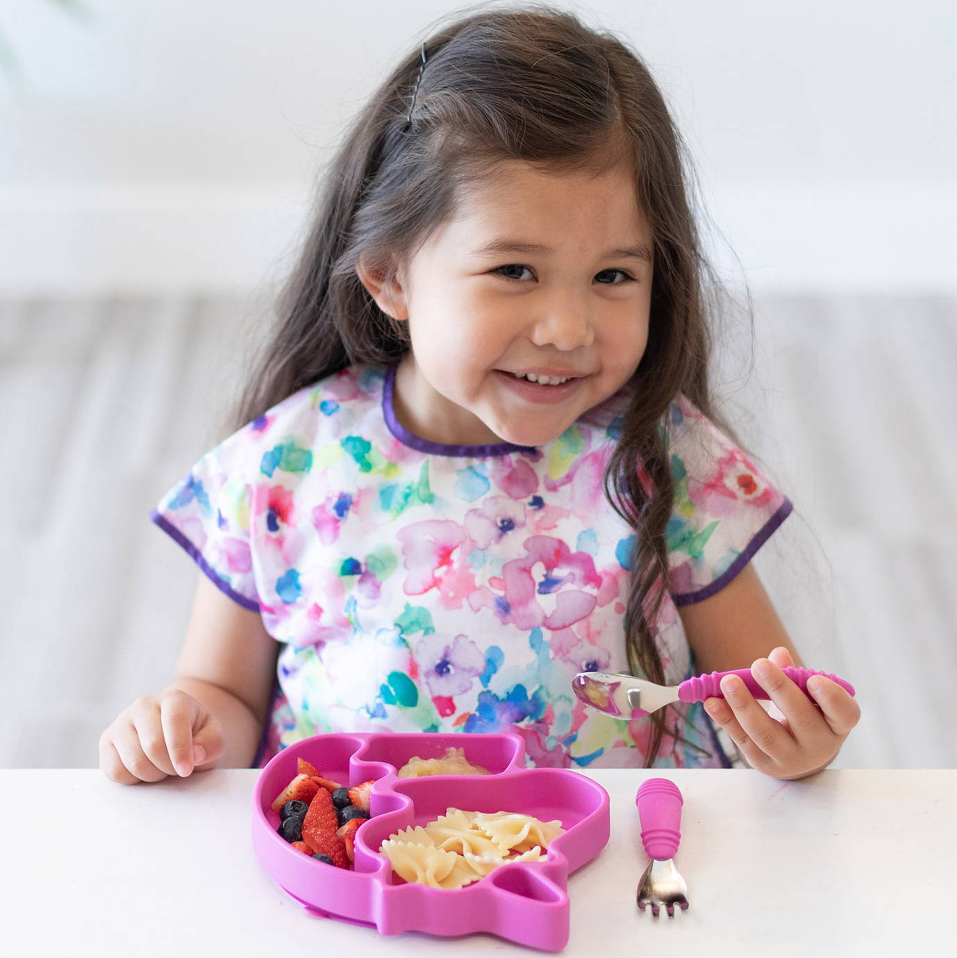 young girl eating out of a bumkins special edition silicone grip dish unicorn and using our bumkins fuchsia colored spoon and fork set