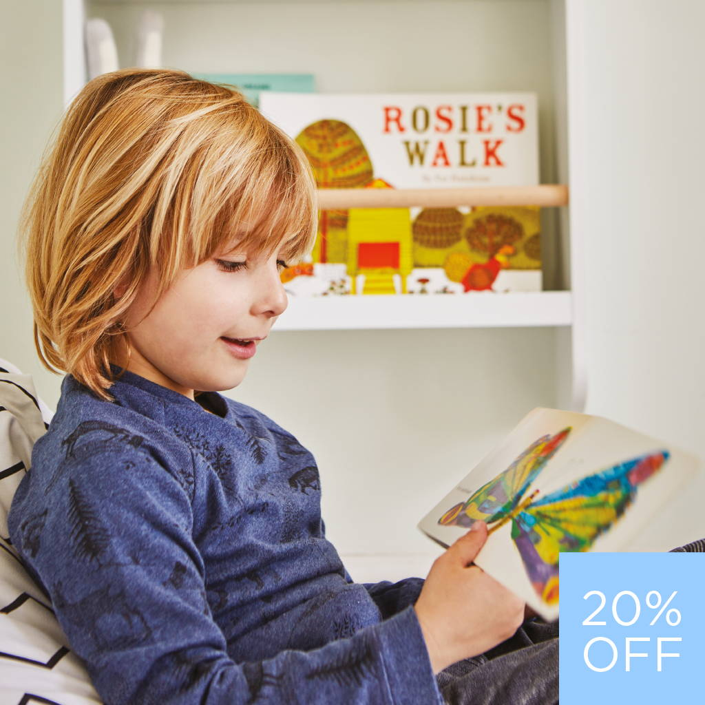 Boy reading book and sitting on a bean bag chair. Also includes a book shelf unit on the wall.