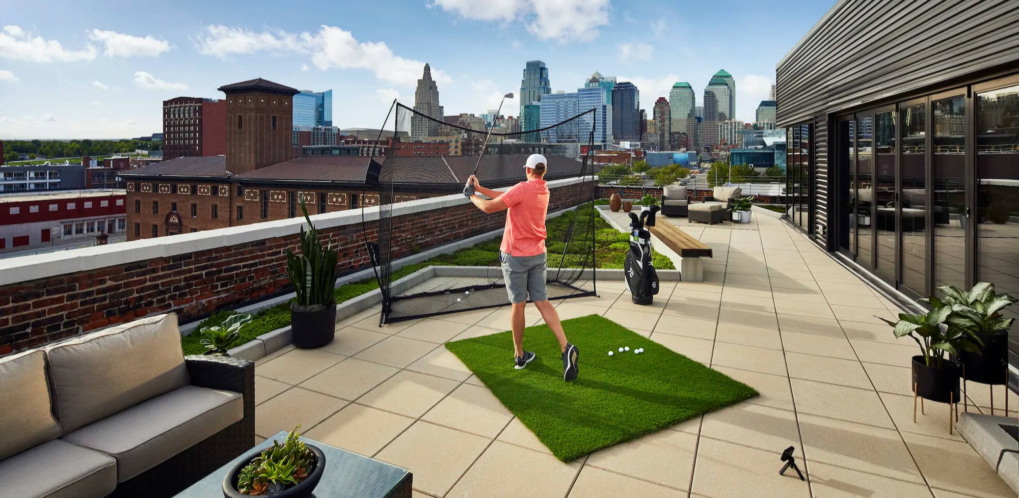 A golfer using the R10  in his rooftop home setup showing the Kansas City skyline