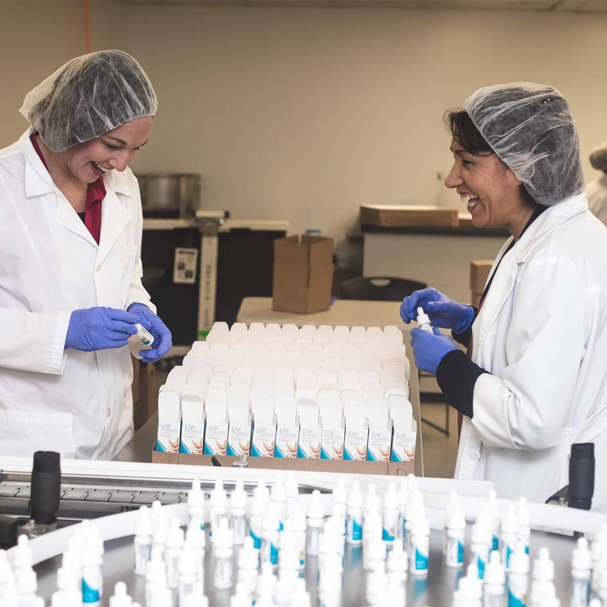 Eosera founder and Manufacturing team lead on manufacturing line filling boxes of EAR PAIN MD for Kids ear drop, ear ache and infection drop and smiling