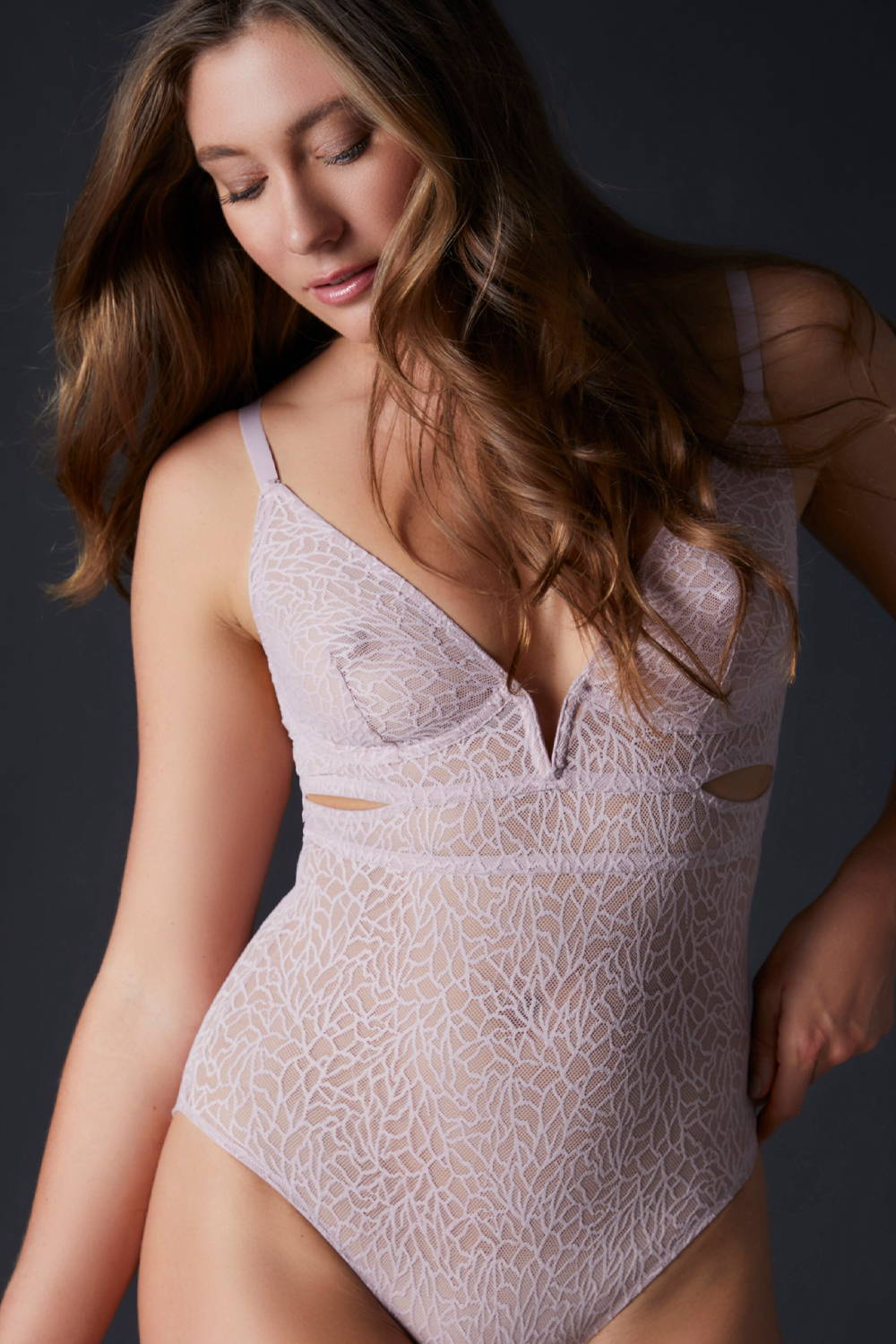 Woman wearing the Else Zoe Bodysuit in pink graphic modern lace on sale for an additional 70% off