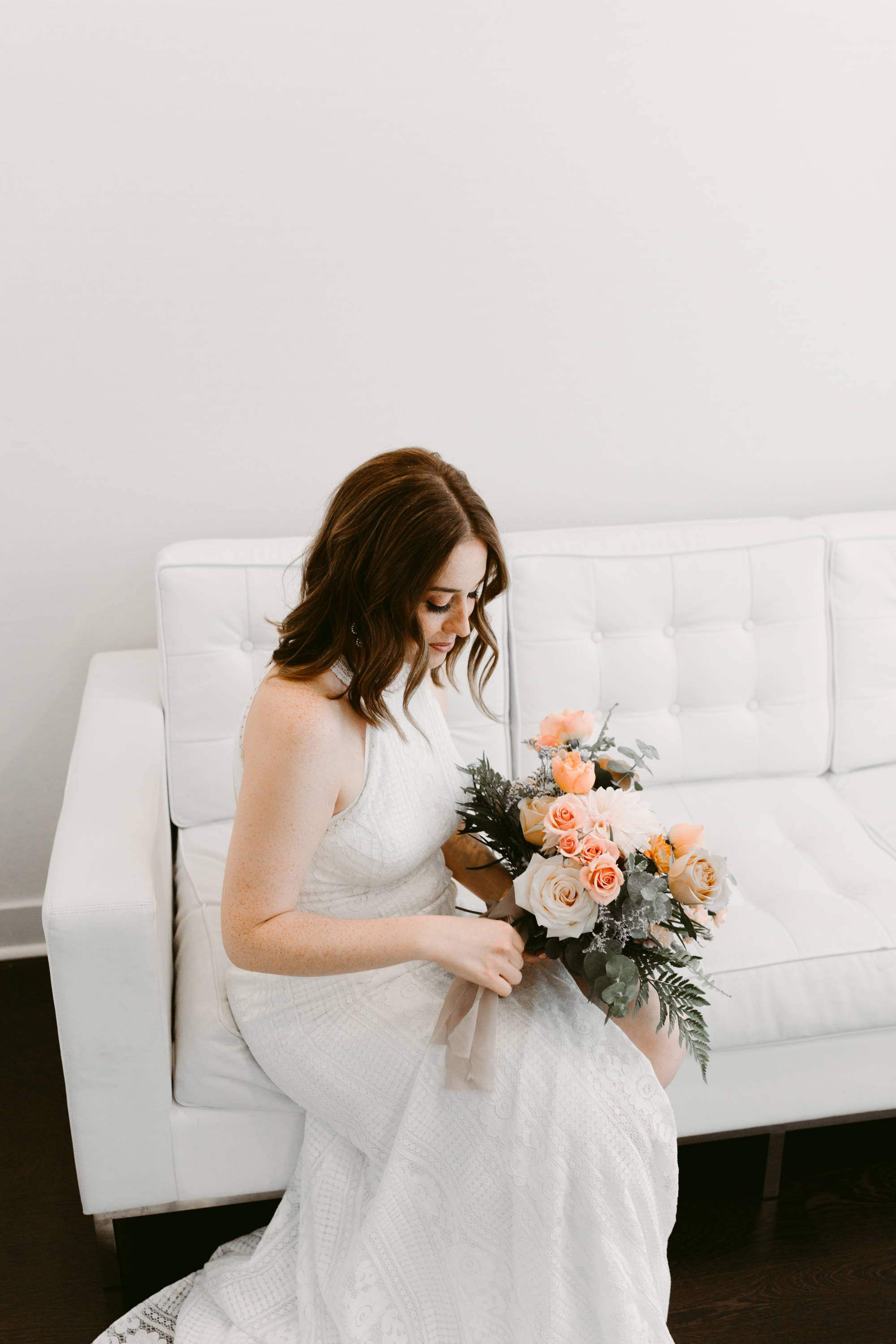 A bride sitting with her bouquet at The Drake Hotel in Toronto