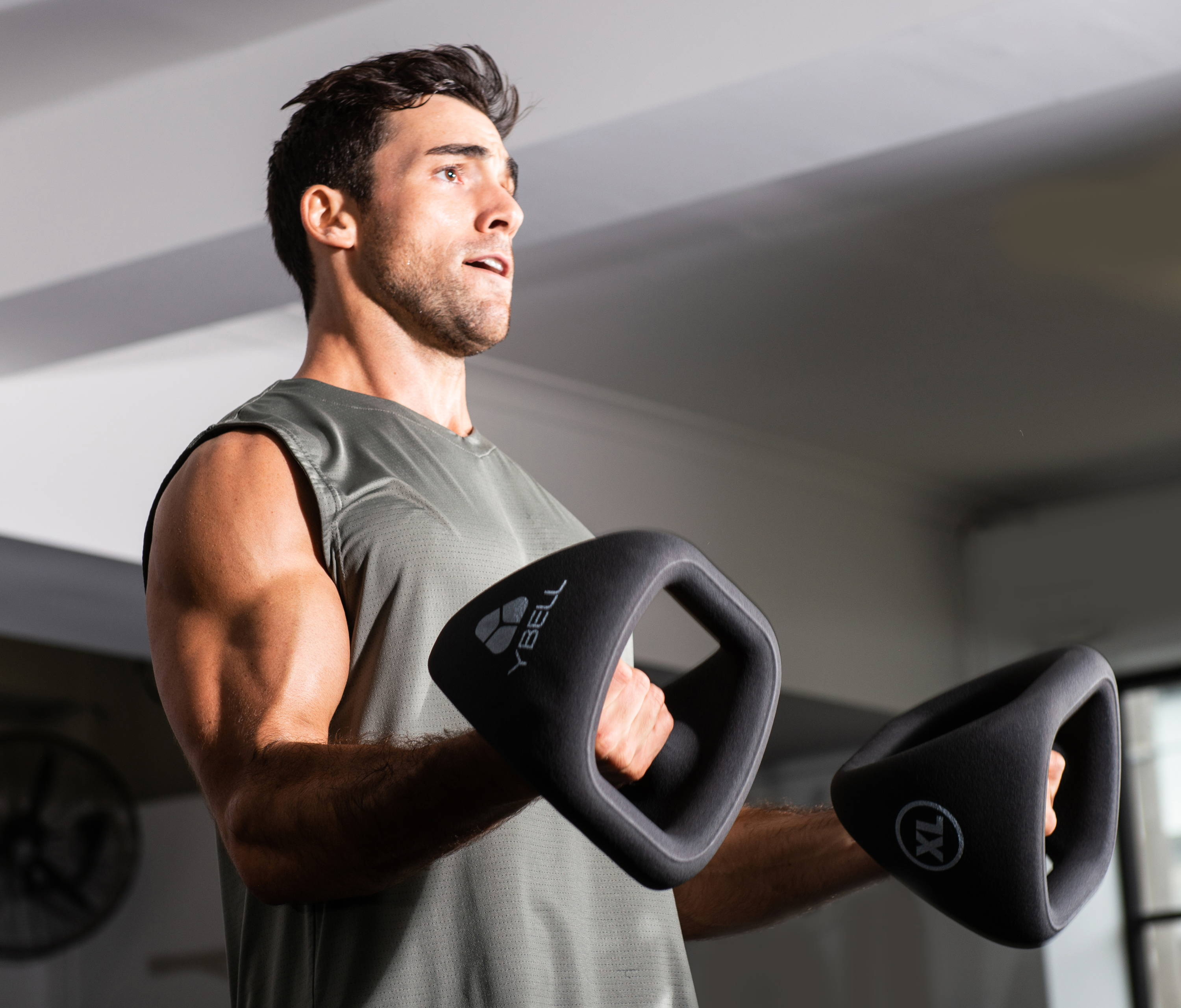 A man working out with YBells in a home gym.