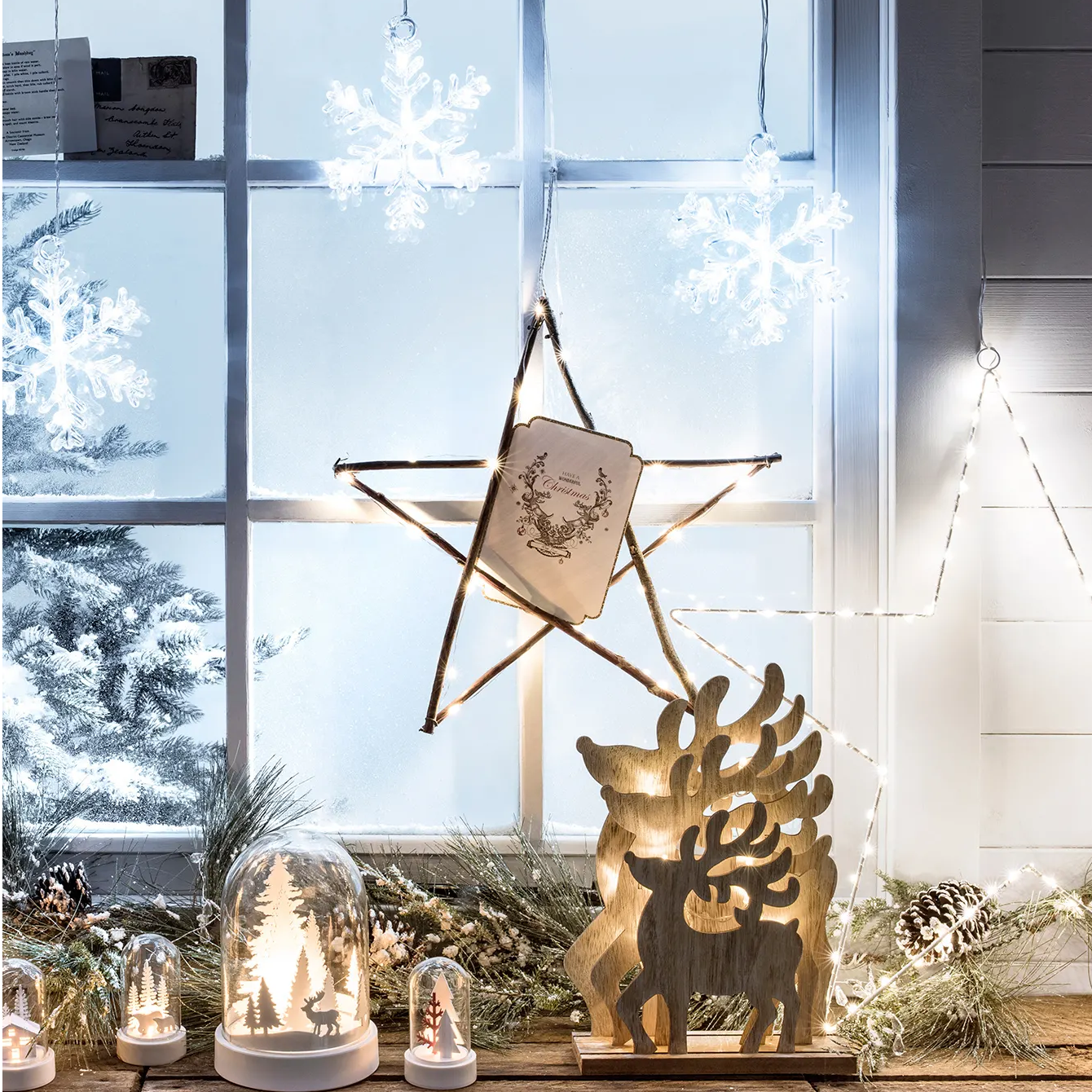 Stockholm Snowflake Christmas Window Light hanging above a window display of wooden ornaments