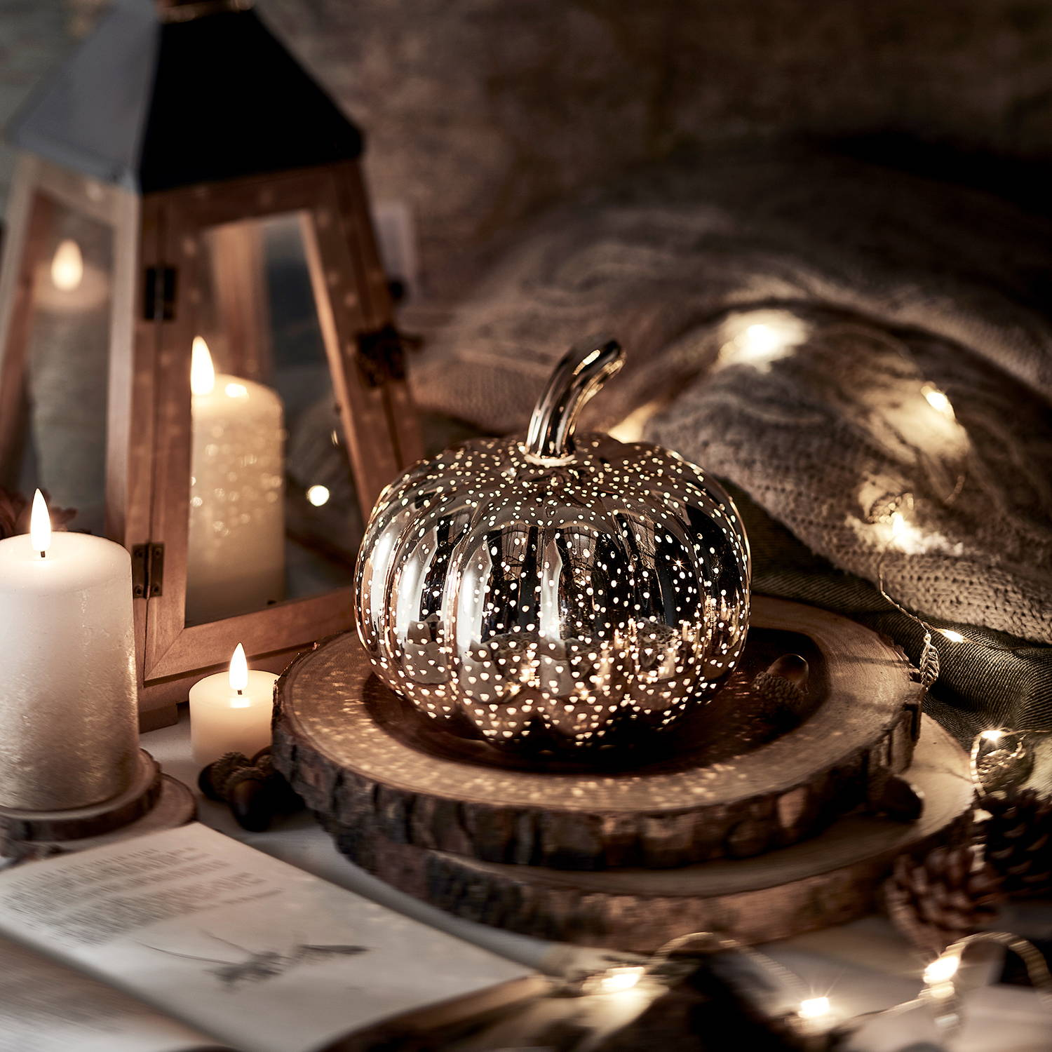 Mottled rose gold pumpkin with illuminate candles and indoor lantern on table