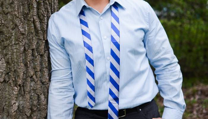 Man wearing an untied blue and silver striped tie