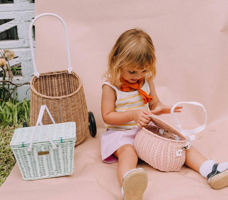 A young girl playing with Olli Ella baskets, which are sold at The Hambledon