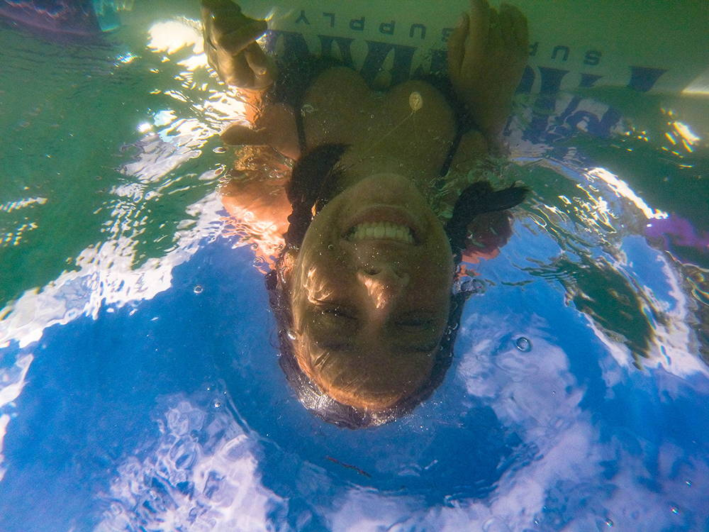 picture from under water looking up at the Pau Hana Moonmist TPU board and girl