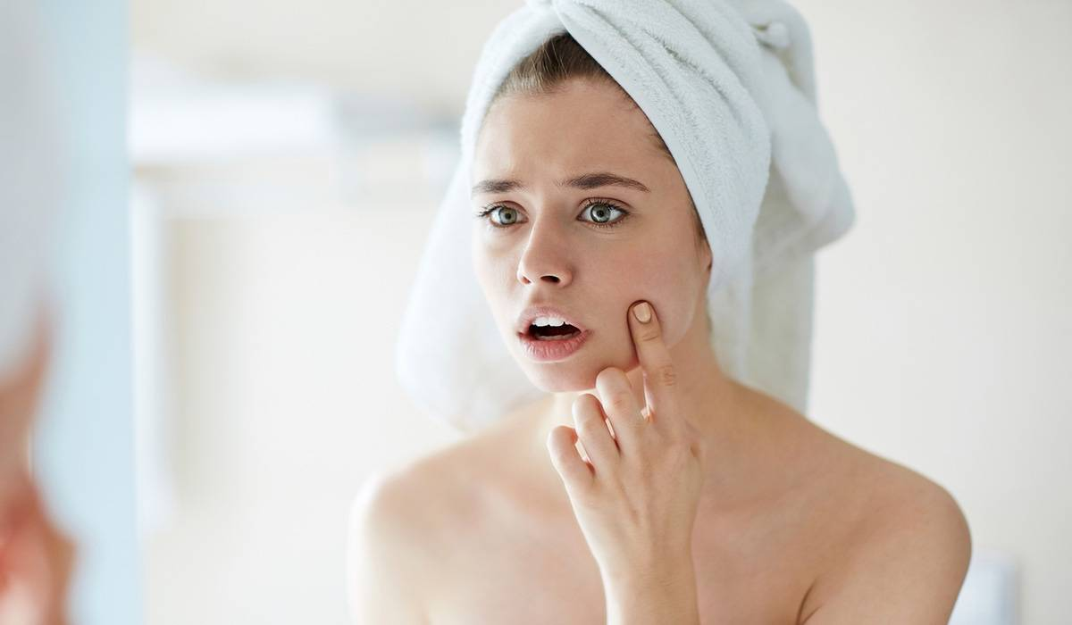 A woman looks in the mirror, towel around her hair, covering a spot with her finger