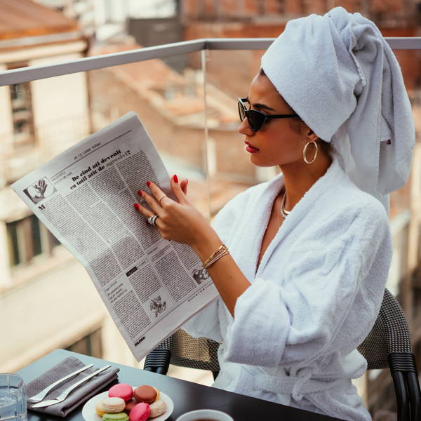 Model wearing various Ring Concierge jewelry while reading a newspaper in a bathrobe on a balcony.