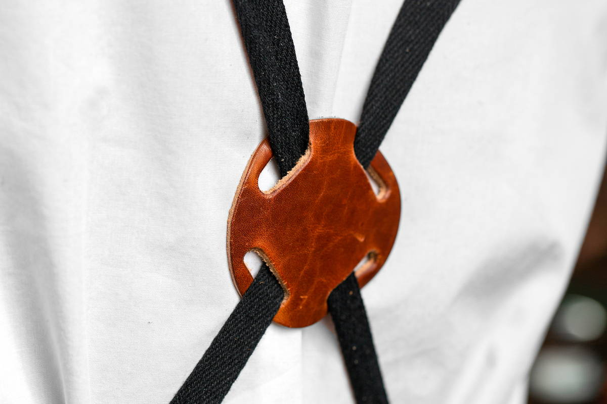 leather accents on green canvas apron